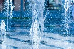 Forsa av vatten av en springbrunn Färgstänk av vatten i springbrunnen, abstrakt bild Royaltyfria Bilder