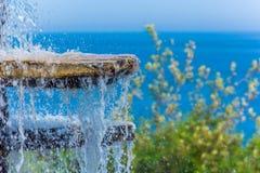 Forsa av vatten av en springbrunn mot det blåa havet royaltyfri foto