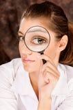 Forscher, der durch Vergrößerungsglasglas schaut Stockbild