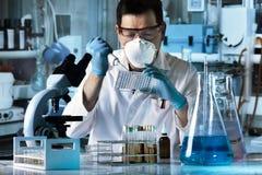 Forscher, der mit microplate im Labor arbeitet lizenzfreie stockfotos