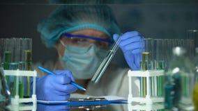 Forscher, der transparente blaue Flüssigkeit, Wasserverschmutzungsverhinderung analysiert stock video