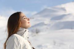 Forscherfrau, die Frischluft im Winter in einem schneebedeckten Berg atmet Stockfotografie