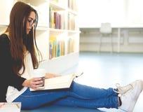 Forskare för ung kvinna som kopplar av med hennes böcker royaltyfria bilder