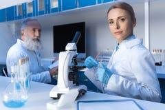 Forskare i det vita laget och skyddande handskar som ser kameran med kollegan Royaltyfria Foton