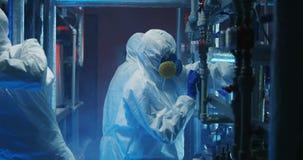 Forskare i hazmatdr?kter som kontrollerar utrustning lager videofilmer