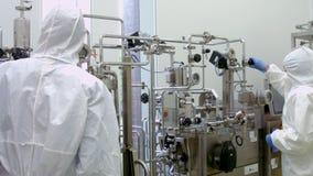 Forskare i skyddande dräkter som arbetar på vaten stock video