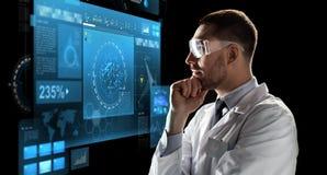 Forskare i skyddsglasögon som ser den faktiska skärmen Royaltyfria Bilder