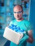Forskare med asken av prövkopior Arkivbild