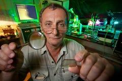Forskare med exponeringsglas, loupe poserar i hans laboratorium Arkivbilder