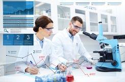 Forskare med skrivplattan och mikroskopet i labb royaltyfria bilder