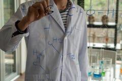 Forskare skriver en kemisk formel med en blå whiteboardpenna på ett klart bräde i laboratoriumet arkivfoto