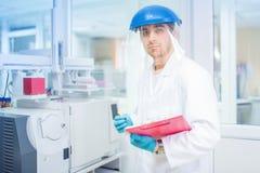 Forskare som använder den skyddande rubber handskar och hjälmen, gör experiment och analyserar i laboratorium Arkivbilder