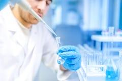 Forskare som använder det medicinska hjälpmedlet för extraktion av flytande från prövkopior i specialt laboratorium eller medicin
