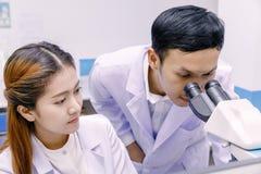 Forskare som använder ett mikroskop i ett laboratorium arkivfoton
