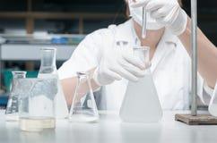 Forskare som arbetar i laboratoriumet som testar prövkopior Fotografering för Bildbyråer