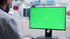 Forskare som arbetar på grön skärmmodellPC i modernt laboratorium stock video