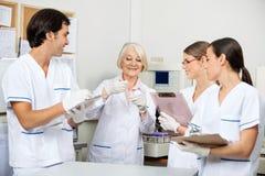 Forskare som diskuterar över prövkopia i laboratorium Royaltyfria Bilder