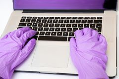 Forskare som gör forskning med den plast- handsken på datoren royaltyfri fotografi