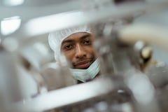 Forskare som kontrollerar utrustning i biotech industri Royaltyfria Bilder