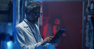 Forskare som kontrollerar utrustning och anv?nder minnestavlan stock video