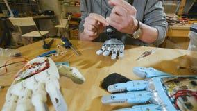Forskare som monterar den innovativa cybernetic robotic armen i techlaboratorium Högteknologisk innovativ teknologi lager videofilmer