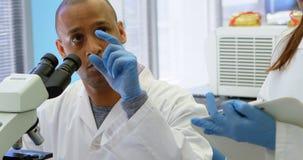 Forskare som påverkar varandra med hans kollega, medan genom att använda mikroskopet 4k stock video
