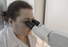 Forskare som ser till och med ett mikroskop i ett laboratorium som gör forskning royaltyfria bilder