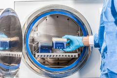 Forskare som steriliserar laboratoriummaterial Royaltyfria Foton