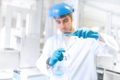 Forskaredoktor som använder laboratoriumflaskan för att ta prövkopior från provröret royaltyfria bilder