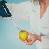 Forskaredoktor som injicerar äpplet Gm-mat Royaltyfri Fotografi