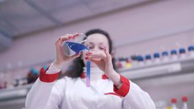 Forskaren blandar flytande i provrör lager videofilmer