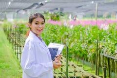 Forskaren f?r den unga kvinnan i en vit kl?nning och unders?ker tr?dg?rden, innan han planterar en ny orkid? arkivbilder