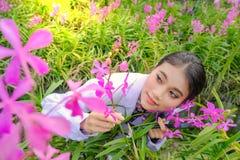 Forskaren f?r den unga kvinnan i en vit kl?nning och unders?ker tr?dg?rden, innan han planterar en ny orkid? royaltyfri fotografi