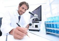Forskaren g?r en anm?rkning av experiment i laboratoriumet royaltyfria bilder