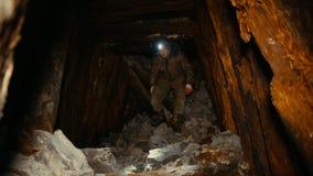 Forskaren med en ficklampa går runt om den kollapsande minen lager videofilmer