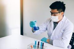 Forskaren med utrustning och vetenskap experimenterar i laboratorium royaltyfri bild