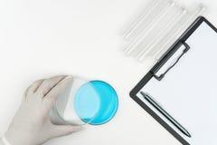 Forskaren som öppnar ett blått vätskeklockaexponeringsglas arkivbild