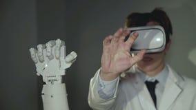 Forskaren som testar den robotic handen, använde vrexponeringsglas i labbet 4K stock video