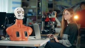 Forskarerobotteknikarbeten med en bärbar dator som kontrollerar en robot Tekniker som arbetar med den futuristiska humanoiden, cy lager videofilmer