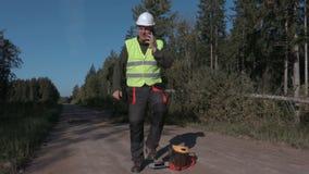 Forstwirtschaftsarbeitskraft, die am Telefon nahe spruce gefallen spricht stock video