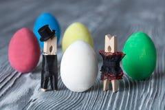 2 forsują pisklęca pojęcia Easter jajek kwiatów trawa malujących umieszczających potomstwa Romantyczna Clothespins para Mężczyzna Fotografia Royalty Free