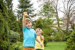 2 forsują pisklęca pojęcia Easter jajek kwiatów trawa malujących umieszczających potomstwa Szczęśliwy śliczny dziecko jest ubrany Zdjęcie Royalty Free