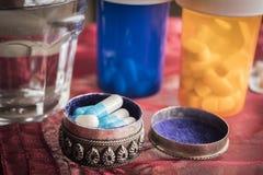 Fortín metálico con las píldoras blancas y azules Foto de archivo libre de regalías