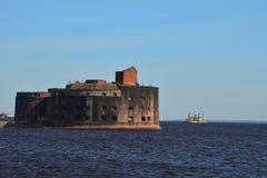 Fort Alexander I i golfen av Finland och ett lastfartyg i Kronstadt, St Petersburg, Ryssland Fotografering för Bildbyråer