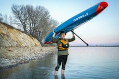 Racing stand up paddleboard by Starboard. Fort Collins, CO, USA - April 22, 2018: Senior paddler is launching his racing stand up paddleboard 2018 All Star by Stock Image