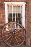 Fort Hubble Trading Post. Old white and iron window to trading post. With a wagon wheel Royalty Free Stock Photos