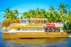 FORT LAUDERDALE, DE V.S. - 11 JULI, 2017: Kleurrijke gele watertaxi met een schitterende mening van de promenadehighrise van de r Royalty-vrije Stock Foto's