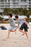 O adolescente trava a bola no jogo de futebol da praia Imagem de Stock Royalty Free