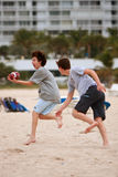 El adolescente coge la bola en partido de fútbol de la playa Imagen de archivo libre de regalías