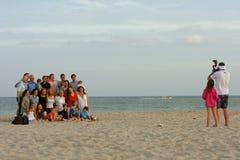 Pose della grande famiglia per la foto sulla spiaggia al crepuscolo Fotografia Stock Libera da Diritti
